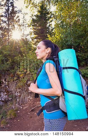 Portrait of a young woman backpacker with backpack in forest, profile.