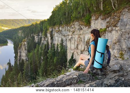 Young woman hiker with backpack sitting on edge of cliff at high altitude.