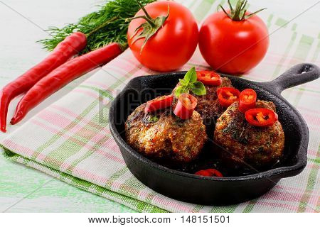 Beef meatballs with chili pepper served in skillet. Grilled bbq meatloaf. Barbecue meatballs.
