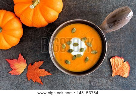Pumpkin Soup Topped With Pumpkin Seeds And Cream On A Stone Background With Autumn Leaves