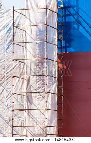 Scaffolding on boat. Ship under construction. Renovation work with protection sheet.