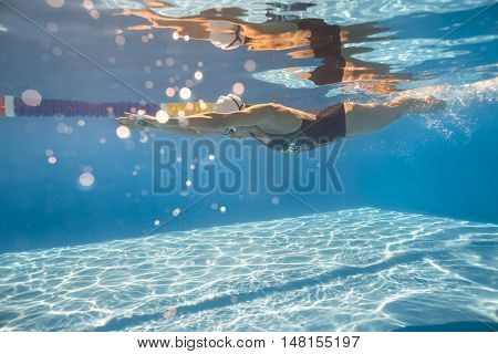 Active swimmer swims in crawl style underwater in the swimming pool outdoors. She wears swimsuit, swim cap and swim glasses. Her body reflected in water surface. Sunlight falls from above. Horizontal.