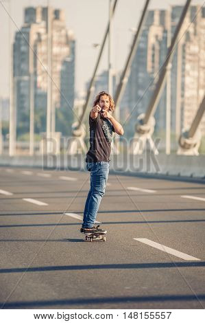 Skateboarder Standing On The Bridge And Pointing To You With His Hand