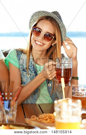 Young woman with glass of beer having fun
