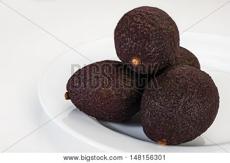 Image if ripe avocados placed on plate with white background