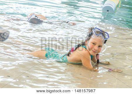 young happy smiling girl swimming in water pool