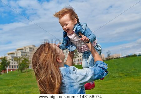 Happy smiling mother holding young toddler daughter in air against sky