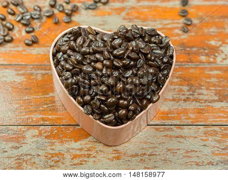 Coffee beans in heart-shaped box and spilling out of a cup, on Wooden table .