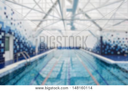 Blurry view of a indoors light swimming pool.