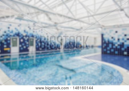 Modern indoor light swimming pool decorated with blue tiles. Blur background.
