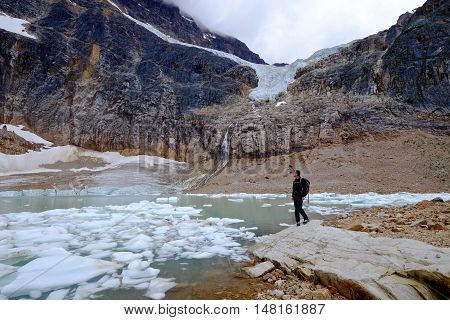 Man ecologist studying melting glacier. Angel Glacier at Mount Edith Cavell. Jasper National Park. Canadian Rockies. Alberta. Canada.