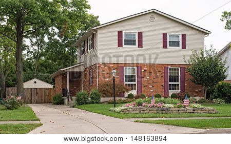 Two Story Brick & Siding House with American Flags