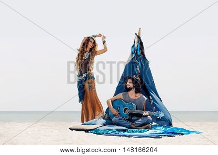 Attractive boho man playing guitar and girl dancing outdoors.Free and happy