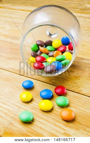 multi-colored and bright candies on a wooden background