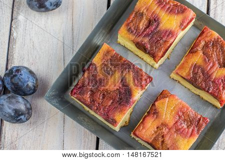 Detailed Top View On Plum Cake With Cinnamon On Small Baking Tray On White Table