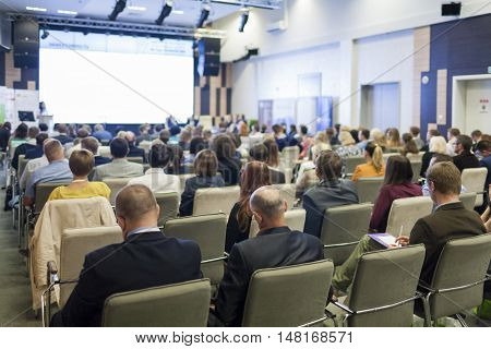 Business Concepts. People At the Conference Listening to Hosts Speakers On Stage. Horizontal Image Orientation