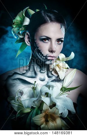Young attractive girl with creative make-up for Halloween. Close-up portrait. Mysterious image of lilies and red eyes.