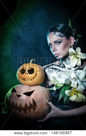 Young attractive girl with creative make-up for Halloween. Portrait close-up pumpkins. Mysterious image of lilies and red eyes. Smoke in the background. Jack-o'-lantern