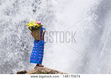 Tribal standing at waterfall with flower seat on timber in Chiang mai, Thailand.