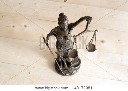 Lady Justice or Themis on wooden table