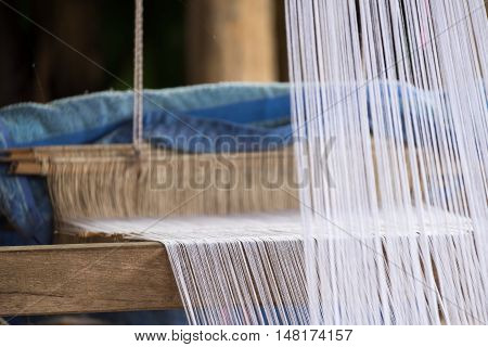 Closeup image an old weaving Loom and thread of yarn. Traditional Handcraft.