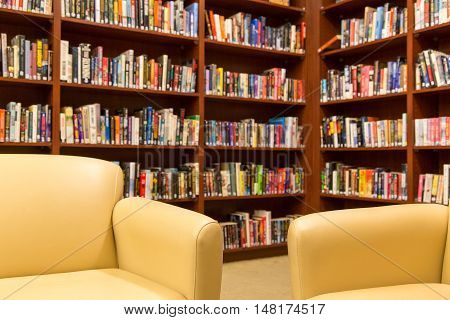 Shallow depth of field focused on chairs with out of focus shelves of of books behind