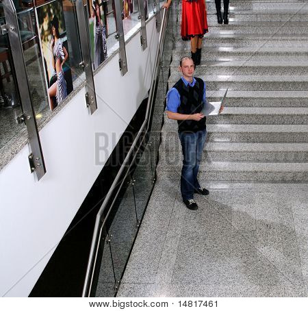 young business man standing on stairs and hold modern laptop