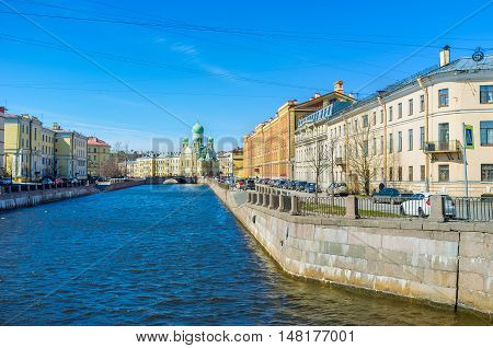 The bright blue waters of Griboedov Canal with the scenic mansions on its banks and St Isidore of Juriev Estonian Orthodox Church in front St Petersburg Russia.