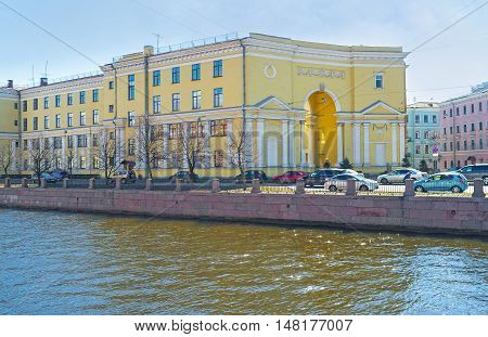 The scenic yellow mansion at the embankment of Griboedov Canal with the giant arch in its corner facade that is slightly concave inward located on Pokrovsky Island St Petersburg Russia.