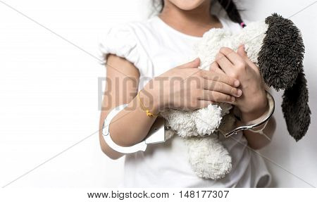 Child holding a doll with her hand in handcuffed copy space