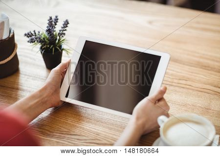 Hands of woman using digital tablet in bakery shop