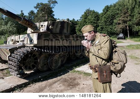 Soldier smokes around the tank. Reconstruction of the War of 1941-1945