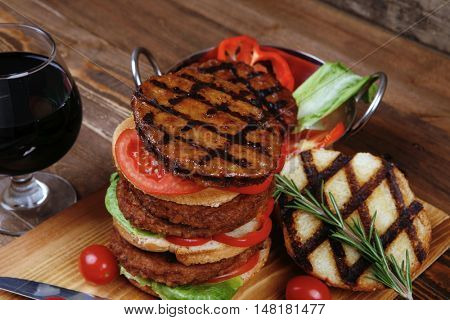fresh grilled beef double huge hamburger served on wooden plate with wine cherry tomatoes and rosemary over table
