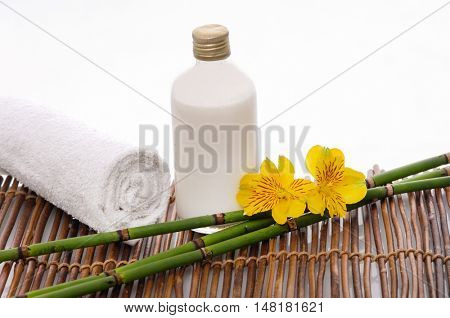 Spa setting with towel ,orchid ,grove,oil on mat