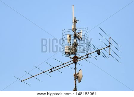 television antenna and wi-fi transmitter on the roof against blue sky