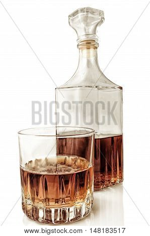 Glass and decanter with alcohol on a white background with reflection. Vertical format. Indoors. Color. Photo.