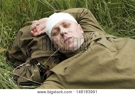 Wounded soldier at rest lies in the grass