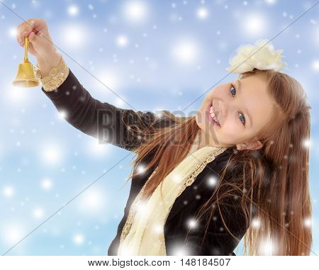 Joyful little long-haired girl with a white rose in her hair, rings the bell. Close-up.Blue Christmas background with white snowflakes.