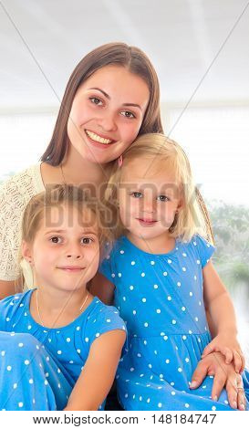 Beautiful young mother with her two daughters. Girls in the same dress with polka dots. Look directly at the camera.The concept of family happiness and mutual understanding between parents