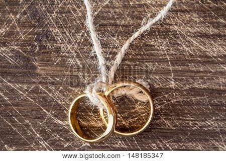 Wedding rings hanging on rope over wooden background.