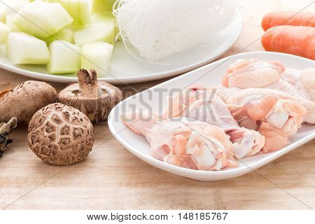 Raw chicken legs with fresh vegetable on wooden.