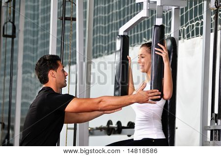 Frau in der Fitness Gim working out with personal Trainer Trainer