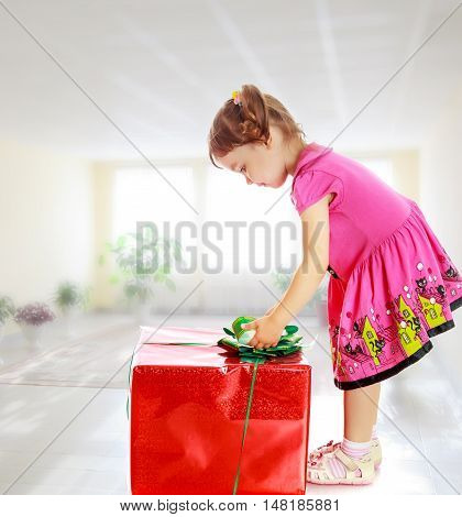The concept of harmonious development of the child in kindergarten. On the background of the hall large Windows.Cute little girl in a pink dress, turned sideways and bent over a large box