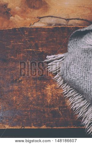 Winter cozy concept style Card - knitted wool scarf over wooden background with copy space in vintage rustic style