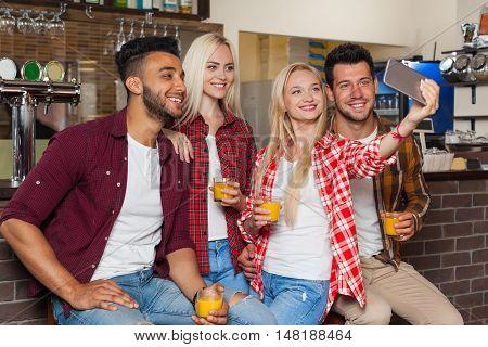 People Friends Taking Selfie Photo Drinking Orange Juice, Sitting At Bar Counter, Mix Race Man Woman Hold Smart Phone Happy Smile Communication