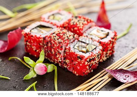 Sushi Roll with Shrimp, Smoked Eel, Avocado and Cream Cheese inside. Tobiko and Sesame outside