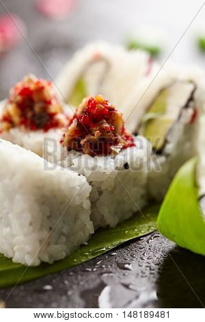 Japanese Cuisine - Sushi Roll with Avocado and Cream Cheese inside. Topped with Smoked Eel and Tobiko