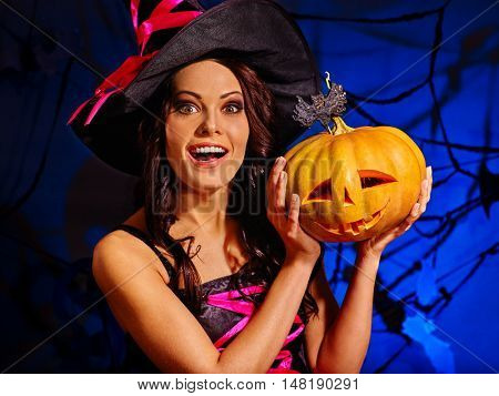 Portrait of Halloween happy witch holding big pumpkin. Witch in hat on Halloween.