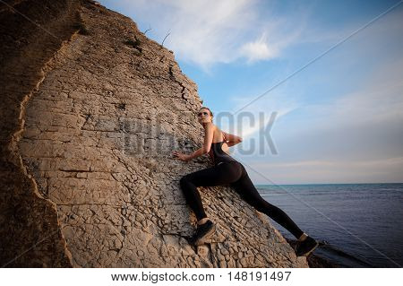 A young woman climbing on the rock. photo from the ground