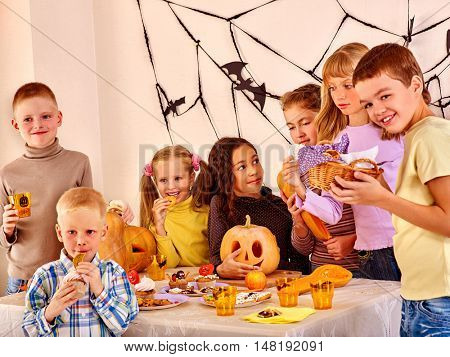 Halloween party with group children holding trick or treat. Celebrating Halloween at Halloween table.